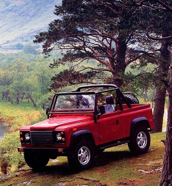 A convertible Land Rover Defender 4x4 in red